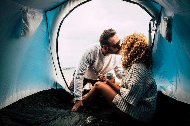 Viaggiatori che si baciano in una tenda in spiaggia