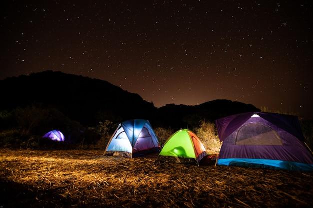 Le tende dei viaggiatori nel mezzo della montagna di notte con le stelle nel cielo.
