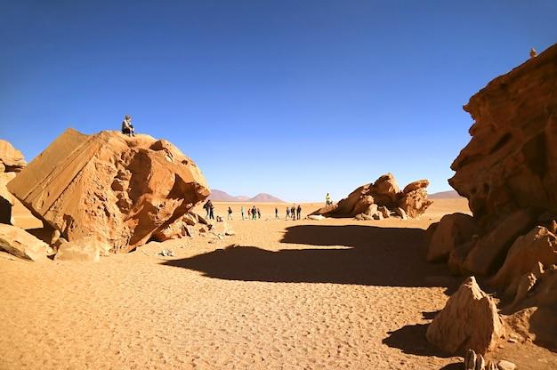 Viaggiatori che visitano incredibili formazioni rocciose nella riserva nazionale della fauna andina di eduardo avaroa bolivia