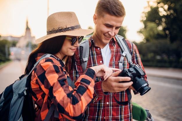 I viaggiatori con gli zaini guardano le foto scattate. escursioni estive. escursione all'avventura di una giovane coppia