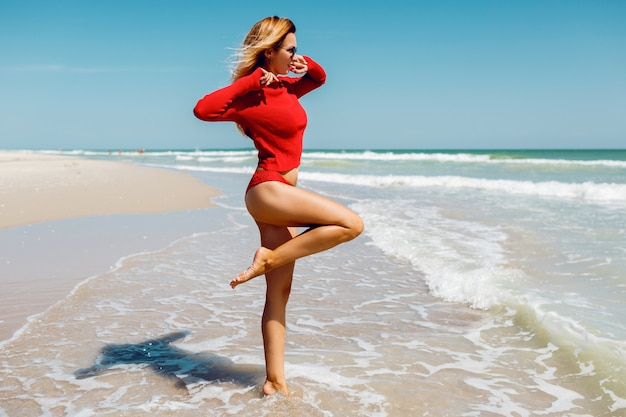 Donna bionda in viaggio che salta con espressione felice, si gira in acqua.