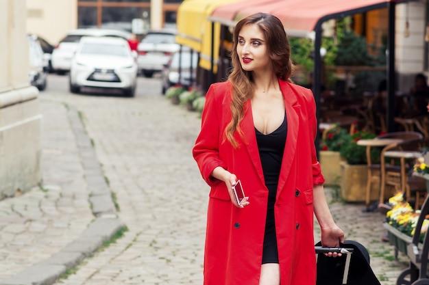 Donna d'affari in viaggio che indossa mantello rosso cammina per strada cittadina.