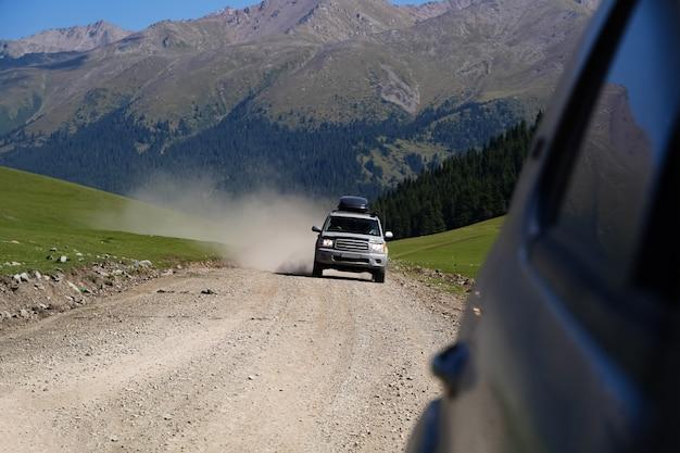 Viaggiare in auto su una polverosa strada di montagna. foto di alta qualità
