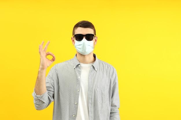 Concetto di viaggio durante il coronavirus con giovane su sfondo giallo.