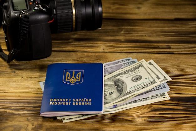 Concetto di viaggio con passaporto ucraino, dollari e moderna macchina fotografica digitale sulla scrivania in legno. modello