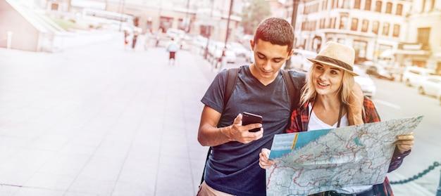 Viaggiare coppia con telefono e mappa sulla strada