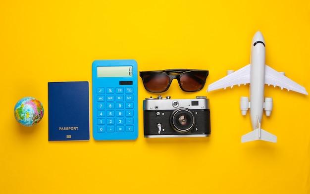 In viaggio. lay piatto. accessori da viaggio, calcolatrice, statuetta di aeroplano su un giallo. viaggio intorno al mondo