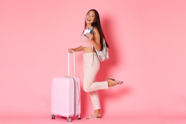 Viaggi, vacanze e concetto di vacanza. a figura intera di ragazza asiatica spensierata, studente di scambio o turista con zaino e valigia, sorridente ampiamente e in possesso di passaporto con biglietti aerei