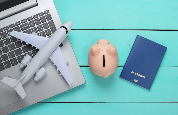 Idea di viaggio. viaggio in linea. computer portatile con salvadanaio, passaporto, aereo su una superficie di legno blu. vista dall'alto