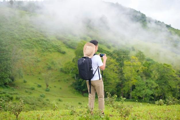 Un uomo in viaggio che gode e si rilassa sulla splendida vista sulle montagne verdi nella stagione delle piogge, clima tropicale.