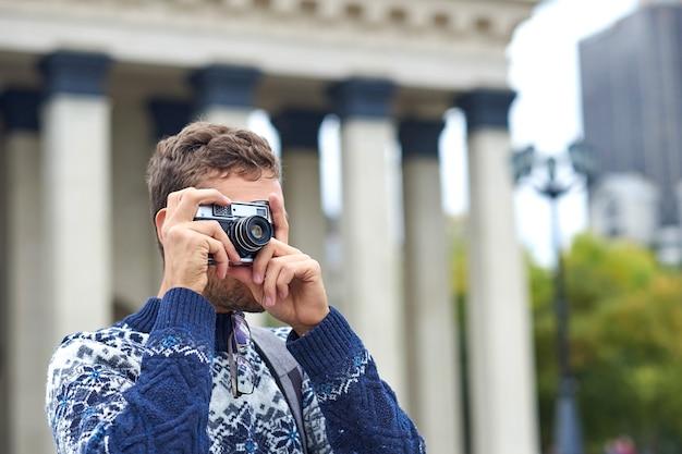 Viaggiatori con zaino e sacco a pelo turistico dell'uomo in viaggio che prendono foto sulla retro macchina fotografica in una città con architettura antica