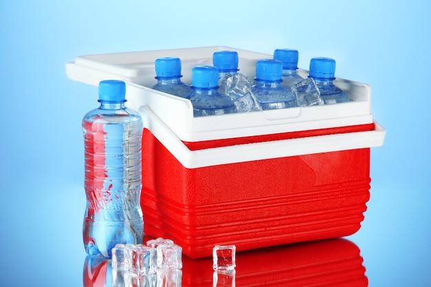 Frigorifero da viaggio con bottiglie d'acqua e cubetti di ghiaccio, su blu