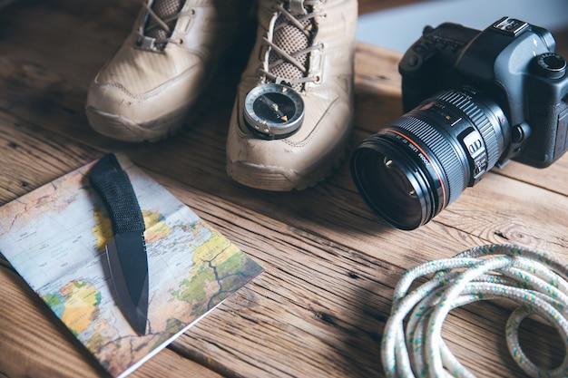Scarpa da viaggio e bussola con fotocamera sul tavolo