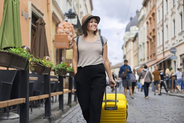 Turista sorridente della donna matura in viaggio in cappello con zaino e valigia camminando lungo la strada della città vecchia, giornata di sole estivo, spazio di persone a piedi