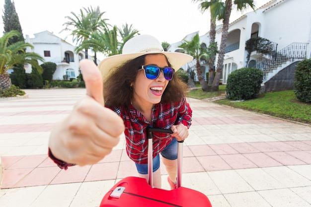 Vacanze in viaggio, vacanze, viaggio e concetto di persone. turista della donna con la valigia che mostra pollice in su quando è arrivata in hotel.