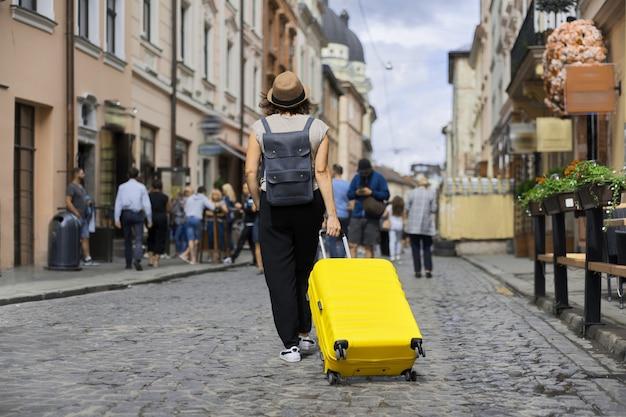 Turista della donna in viaggio in cappello con zaino e valigia che cammina lungo la strada della vecchia città turistica, vista posteriore di giorno pieno di sole di estate, sfondo di persone a piedi