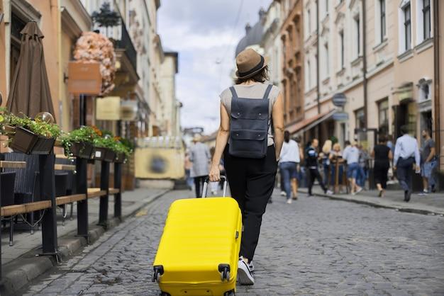 Turista in viaggio con cappello con zaino e valigia che cammina lungo la strada della vecchia città turistica, vista posteriore di una giornata di sole estivo, sfondo di persone che camminano