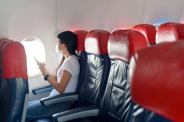 Una donna in viaggio che indossa una maschera protettiva a bordo dell'aereo utilizzando lo smartphone, viaggia sotto la pandemia covid-19, viaggi di sicurezza, protocollo di allontanamento sociale, nuovo concetto di viaggio normale
