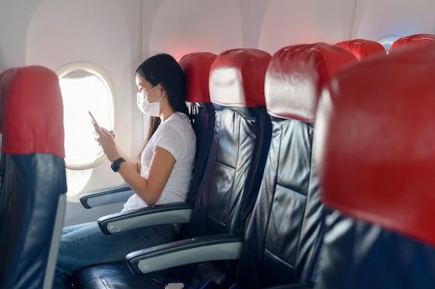 Una donna in viaggio che indossa una maschera protettiva a bordo dell'aereo utilizzando lo smartphone, viaggia sotto la pandemia covid-19