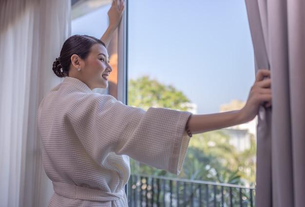 Sorriso di bella donna asiatica del viaggiatore per guardare laggiù rimanere vicino alla porta nella camera d'albergo