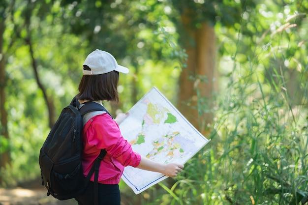 Escursionismo viaggiatore, donne che leggono la mappa e viaggiano nella foresta