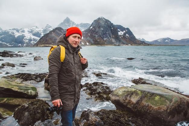 Fotografo professionista del viaggiatore che prende la foto della natura del paesaggio. indossa uno zaino giallo con un cappello rosso in piedi sulle rocce sullo sfondo del mare e delle montagne. spazio per te