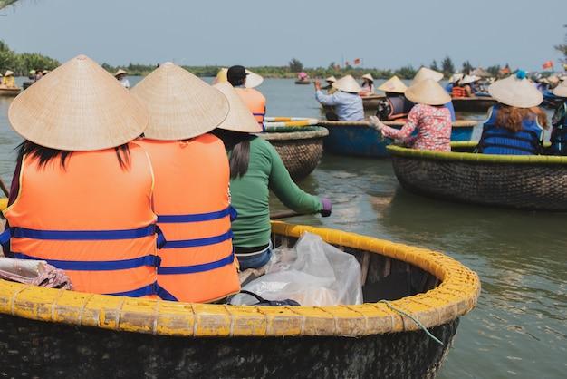Viaggiatore che si siede nella barca di canestro di bambù tradizionale del vietnam nel canale a da nang, vietnam.