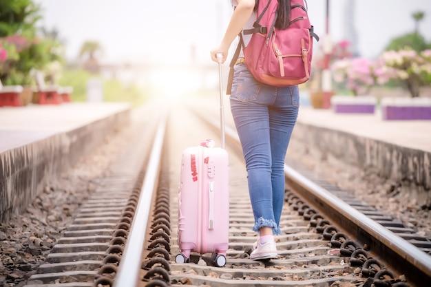 Viaggiatore che cammina alla stazione ferroviaria prima del viaggio. lavoro e concetto di viaggio.