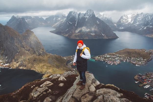 Viaggiatore che indossa uno zaino giallo in piedi sulle rocce sullo sfondo del mare e delle montagne. spazio per il tuo messaggio di testo o contenuto promozionale. concetto di stile di vita di viaggio.
