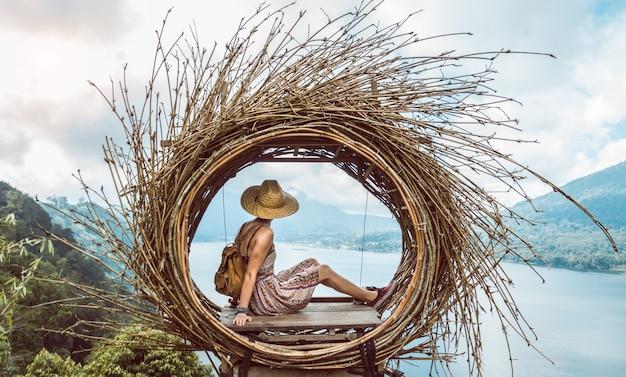 Cappello della holding della donna del viaggiatore che si siede guardando il paesaggio della natura delle montagne che si sentono liberi