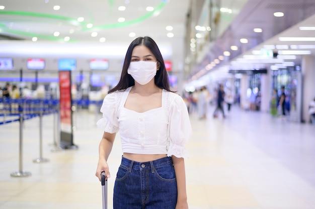 Una donna viaggiatrice indossa una maschera protettiva in aeroporto internazionale, viaggia sotto pandemia covid-19, viaggi di sicurezza, protocollo di allontanamento sociale