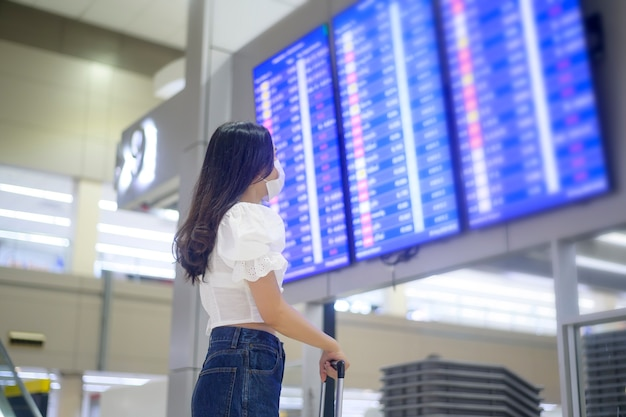Una donna viaggiatrice indossa una maschera protettiva all'aeroporto internazionale, viaggia sotto la pandemia covid-19