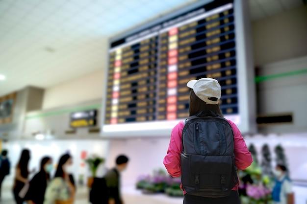 Donna del viaggiatore che osserva al programma di volo all'aeroporto di donmuang bangkok tailandia