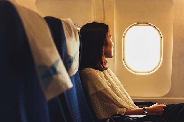 Donna del viaggiatore che si siede in aeroplano che guarda fuori attraverso la finestra.