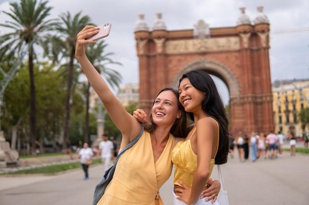 Amiche in viaggio che prendono selfie in città