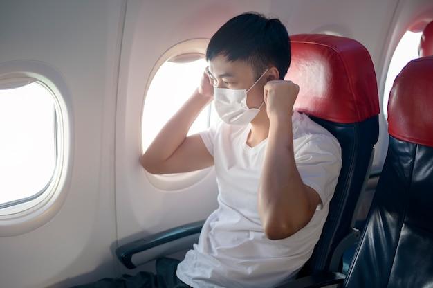 Un uomo in viaggio indossa una maschera protettiva a bordo dell'aereo, viaggia sotto pandemia covid-19, viaggi sicuri, protocollo di allontanamento sociale, nuovo concetto di viaggio normale