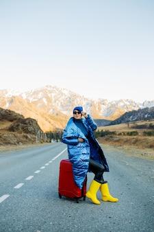 Donna in viaggio in giacca blu e cappello e stivali gialli luminosi che si siede sulla valigia rossa sulla strada di montagna