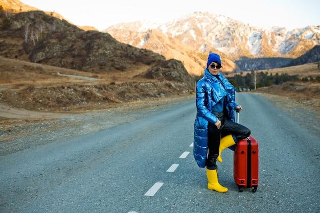 Donna in viaggio in giacca blu e cappello e stivali gialli luminosi con la valigia rossa sulla strada di montagna