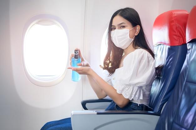 Una donna in viaggio indossa una maschera protettiva e si lava le mani con del gel alcolico a bordo