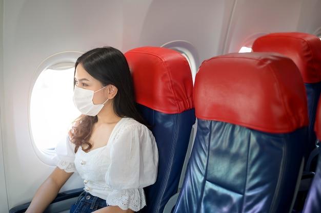 Una donna in viaggio indossa una maschera protettiva a bordo dell'aereo, viaggia sotto pandemia covid-19, viaggi sicuri, protocollo di allontanamento sociale, nuovo concetto di viaggio normale
