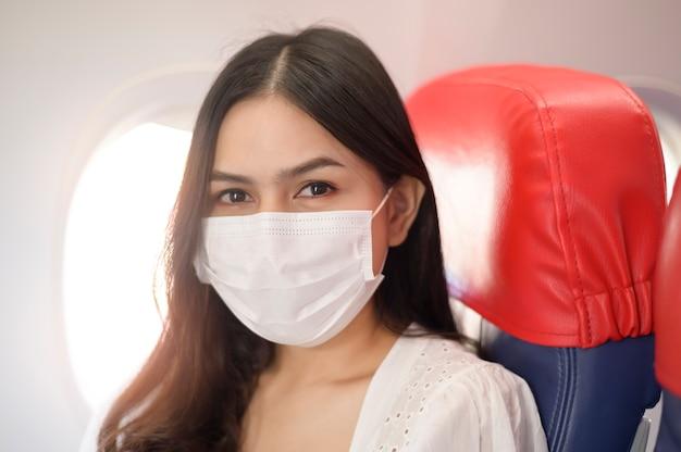 Una donna in viaggio indossa una maschera protettiva a bordo dell'aereo, viaggia sotto pandemia covid-19, viaggi sicuri, protocollo di allontanamento sociale