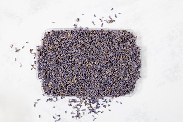 Vassoio pieno di semi di lavanda fiori biologici e incensi aromatici per creare bustine naturali