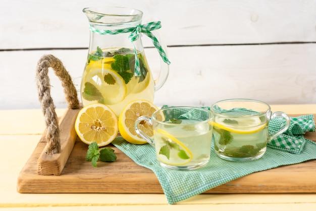 Su un vassoio è appena fatta la limonata in una caraffa di vetro.