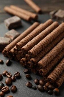 Vassoio con rotoli di wafer al cioccolato, chicchi di caffè e cioccolato, da vicino