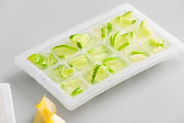 Vassoio con agrumi in ghiaccio su superficie colorata