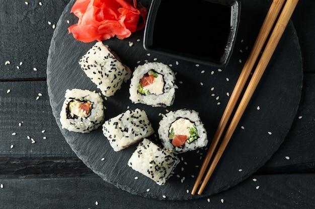 Vassoio con deliziosi rotoli di sushi su superficie di legno. cibo giapponese