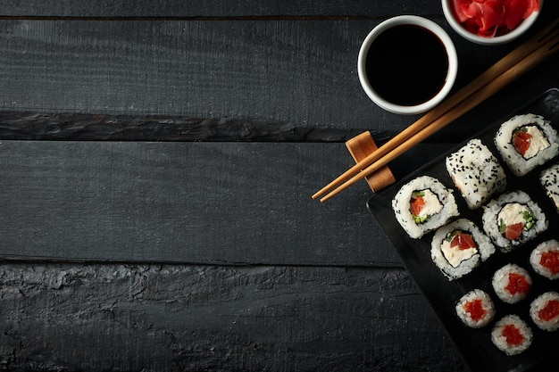 Vassoio con i rotoli di sushi deliziosi sulla tavola di legno, vista superiore. cibo giapponese