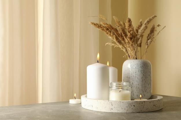 Vassoio con candele profumate e canna sul tavolo grigio