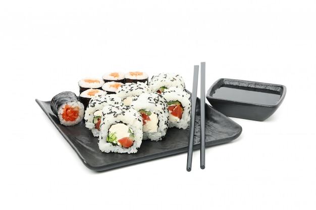 Vassoio con involtini di sushi, bacchette e salsa di soia isolato su superficie bianca