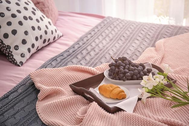 Vassoio con gustosa colazione e fiori sul letto
